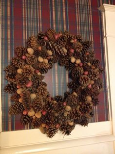 A pine cone and nut wreath is a nice neutral against the plaid wall paper in the library.