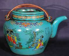 Antique Chinese kettle made of ceramic. Hand painted with decorative asian women and flowers.