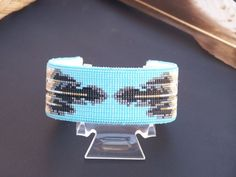 This American Indian beaded bracelet with the Feather pattern is made with the blends of the colors of black, tarnished silver, creams and grays with a blue turquoise back drop. The base used for this