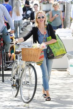 Naomi Watts wheels her bike while sporting a classic pair of overalls. via StyleList