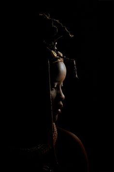 Africa | A Himba woman photographed in her hut | © Jonathan Tolleneer