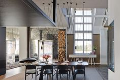Suspended fireplace and lighting from the soaring ceilings. Firewood storage and branches add a natural feel to the space. Contemporary dining set adds elegance.