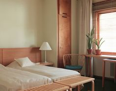 A bedroom in Alvar Aalto's Helsinki home with his modern classic Artek Bench at the foot of each bed.