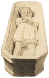 Post mortem picture of a baby in his coffin. Happily it has enough room for him. Sometimes the little ones are so propped up, as you can see on several photo's on this site.
