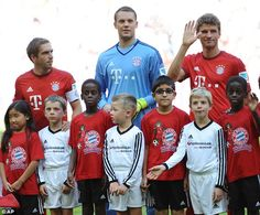 Show of solidarity:Bayern Munich footballers, including (L-R) Philipp Lahm, goalkeeper Manuel Neuer and Thomas Mueller took to the pitch with migrant mascots today in a show of solidarity with the thousands of refugees entering Germany