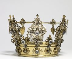 Although crowns are customarily associated with royalty, wedding crowns in Scandinavia were worn by brides of all social strata. They were owned by the bride's parish and loaned for the occasion. Wedding crowns were richly decorated with emblems of conjugal love: this example includes carnations, linden leaves, representing fertility, and angels. The crown itself resembles that worn by Mary, Queen of Heaven. Early 18thc. Silvergilt with paste jewels.