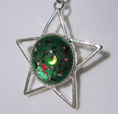 """Alle"" Star Fairy Gem Pendant.  Gorgeous Fairy Gem with forest green background, and multiple glitters in red, pink, black, and more, with gold holographic crescent moons.  Set into a shiny silver tone Star or Pentacle shaped pendant Tray, with complimentary necklace chain.  Completely One ..."