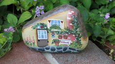 This cottage garden rock was painted a cream color with a fireplace, picnic table, flowers & claypots and more. Etsy, $24