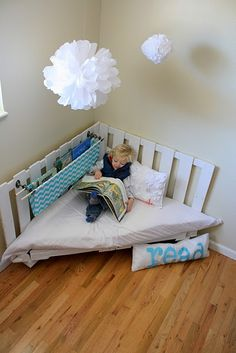I need this in our playroom...A low to the ground corner reading nook means anyone of different sizes or abilities can easily curl up and read alone or together. I think one like this can easily #DIY with #pallets and one or several folded comforters, pillows, foam, etc.