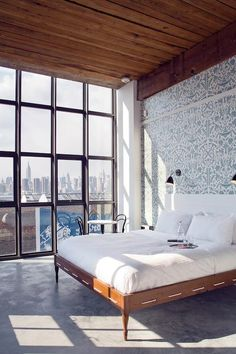 nouveau toile wallpaper, crisp white sheets, timber ceiling, polished concrete floors. love.
