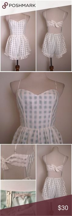 """Lovers + Friends Gingham Ruffled Romper Sz S Lovers + Friends 'Gabriella' romper. Size S. Super cute!   Condition: Good pre-owned condition- small pin hole on the side as shown in the 4th photo (not very noticeable).  // D E T A I L S * Sweetheart neckline * Ruffle hem detailing * White gingham overlay * Tie-back / exposed back * Hidden back zipper closure  // M A T E R I A L Fabric content tag is missing but it feels like polyester.  // M E A S U R E M E N T S * Waist - 14"""" inches across…"""