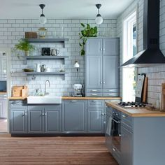 Traditionellt grått kök med BODBYN fronter, porslinsdiskho och fristående enheter med vitrinluckor
