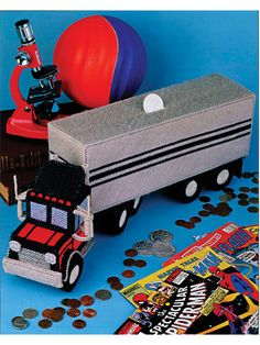 """How to make an 18 wheeler truck bank using plastic canvas pattern This playful piggy bank will help any trucker become a tycoon. Made from stiff and regular 7-mesh plastic canvas and worsted weight yarn, this big rig measures 19 1/2"""" long.  (aff link)"""