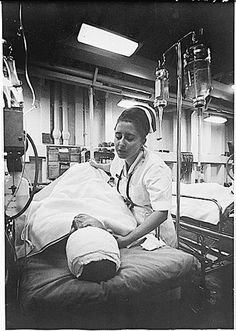 In the South China Sea, a nurse tends a patient just out of surgery in the intensive care ward of the hospital ship USS Repose (AH-16). The ship is steaming off the coast of Vietnam a few miles south of the 17th parallel. (October 1967)