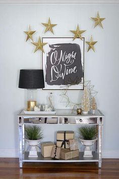 Black and Gold Christmas Decor -- Love the look of the silver mirrored console table, gold lamp and accessories, mini cement urns and potted indoor plants, and the graphic black and white poster print above! The gold glitter DIY hanging stars add a bit of festive holiday sparkle!