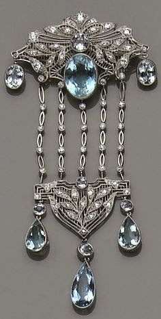 An aquamarine, diamond and platinum brooch, circa 1930's the wide kite-shape top of filigree design, centering a bezel-set round and oval-shaped aquamarines, the foliate motif set with European and single-cut diamonds, suspending on either side an oval-shaped aquamarine, and five diamond-set navette-shaped link chains terminating with a triangular-shaped openwork plaque,