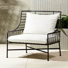 "On sale. Shop Breton Black Metal Chair. Designed by Mermelada Estudio, streamlined chair evokes ""the essence of French coastal living in the 1960's. "" Modern metal frame wears black matte powdercoat, topped with a plush off-white seat and back cushion. Learn about on our blog."