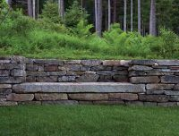 Good way to do a retaining wall, camouflage with stones.  It's also a built in bench..