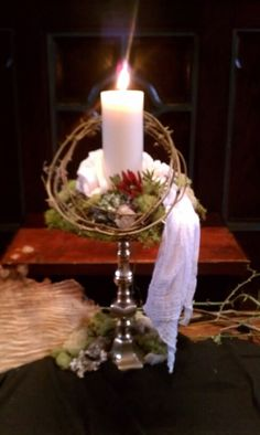 A Good Friday wreath form with crown of thorns. The wreath is covered with sheet moss. Small rocks, reindeer moss, lichen, and dried olives from the Garden of Gethsemane were added. Tea stained scrim represents the grave clothes. A Protea was the only bloom added. It represents the  suffering of Jesus. At the base we added more moss, fantail willow, thornbush canes and a wedge of tree trunk.