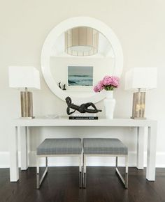 Modern white foyer console with round mirror and two gold accent lamps | blue bench