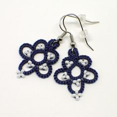 Tatted lace earrings in navy blue featuring white seed bead accents. Theses flower earrings give a nautical feel to your summer outfits. Glass seed beads in opaque white adorn the petals and pop against the navy 100% Egyptian cotton thread. These earrings are shuttle tatted by hand. Tatted lace is extremely lightweight to wear. You will barely know youre wearing these earrings. Tatting is made up of a series of knots, so items wear extremely well.  The lace hangs from silver tone…