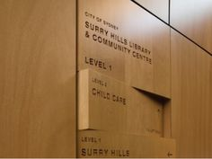 Wood signage design_ shifting panels, wood burned/engraved names lobby directory Sydney library and community center Environmental Graphic Design, Environmental Graphics, Design Stand, Booth Design, Wayfinding Signs, Directional Signage, 3d Signage, Library Signage, Wooden Signage