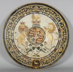 A scagliola table top by Joseph Darmanin & Sons of Malta, 1837, shows the Hanoverian British royal coat of arms within the Garter, supported by the lion and unicorn, surmounted by a lion on a crown beneath national emblems and motto; below, an outer border of thistles and roses with a badge of horse and palm tree. (Royal Collection Trust)