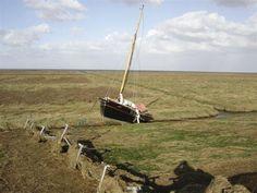 kwelders bij Noordpolderzijl, met door storm aangespoeld zeilbootje