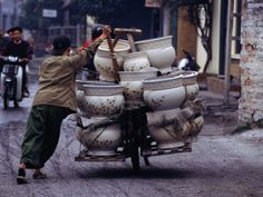 Man transporting locally made ceramic pots by bicycle in Hanoi, Vietnam.