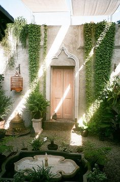 End of the tunnel dreamy courtyard, shade sails ivy, enclosed secret garden feeling, and a fountain