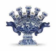 A Dutch Delft Blue and White Tulip vase -   1690-1700 -   The heart-shaped body surmounted by five nozzles of octagonal section, the front with four further nozzles, painted with flowers and foliage centred by a maiden, the reverse depicting a bird, the sides with two winged beast handles, on a flared rectangular foot with scrolling foliage and blue-ground panels, minor chips and losses.  29 cm. high x 33 cm. wide