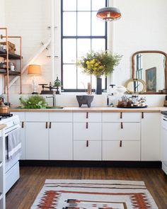 Kitchen - An Ikea kitchen with custom details such as leather pulls, black baseboards, and shelves with copper piping