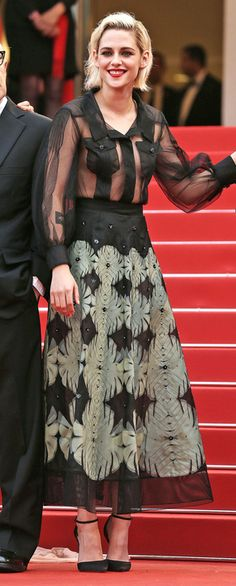 KRISTEN STEWART in a sheer black shirt with opaque panels over her décolletage, plus a tea-length skirt with ivory blooms, at the Café Society premiere and gala opening night. | Cannes Film Festival Red Carpet 2016.