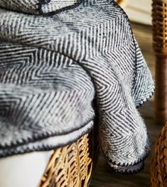 A close-up image of a black and white throw in an armchair.