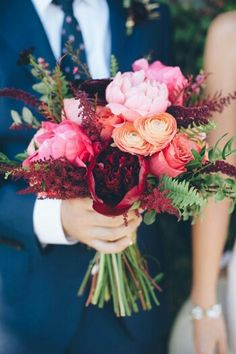 Hand Tied Wedding Bouquet Showcasing: Cranberry Peonies, Pink Peonies, Coral Roses, Peach Ranunculus, Marsala Astilbe, Green Sword Fern & Additional Greenery + Foliage