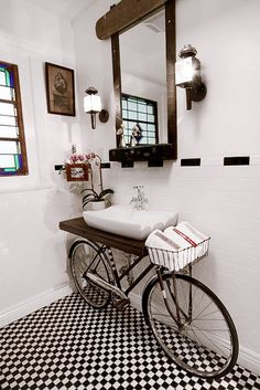 Unique bathroom designed by New Orleans based artist Benjamin Bullins. Old discarded bicycle was repurposed and combined with beautiful counter top (made of salvaged wood), modern sink, and vintage faucet. Creative bathroom vanity. Bicycle basket holds towels and other items.