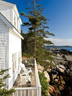 This simple, wooden deck overlooks the shore on Wheaton Island, Maine. Two Adirondack chairs are perfectly situated for taking in the harbor...