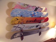 A wooden snowboard rack that stores up to 5 boards in a slotted wall rack.