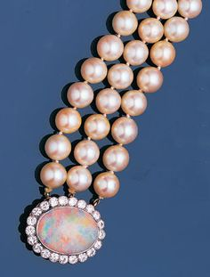 A cultured pearl choker with opal and diamond clasp The three rows of 9.0mm. cultured pearls, to a clasp set with an oval opal within a scalloped border of old brilliant-cut diamonds, length 36.0cm.