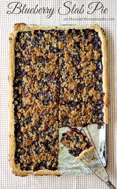 Blueberry Slab Pie – This flaky, single layer pie recipe will be welcome at any party, any time of the year. The crust is filled with plump, juicy blueberries and topped with a crumb topping with pecans. It's delicious!