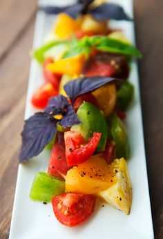 simple summer heirloom tomato salad with olive oil, kosher salt and purple fresh basil. you can cut the tomatoes into chunks or slice thin for carpaccio. how beautiful is the purple basil against the reds, yellows and greens of the tomatoes? so willow.