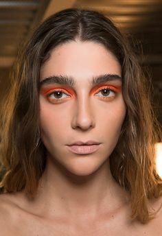 The eyes had it at House of Holland this season, with backstage faces kept au naturel (brushed-up brows and peachy bronzer on the cheeks) to showcase sunset eyeshadow shades with max impact. Neon pops of tangerine were kept blocky and intense, smudged into the corner of the eye and flicking up towards the end of the brow. Then, a softer gradient rimmed the lower lashline for that '80s-bright look, fit for everything from festivals to nights out.