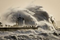 Description of . People watch and photograph enormous waves as they break, on Porthcawl harbour, South Wales, Monday Jan. 6, 2014.  Resident...