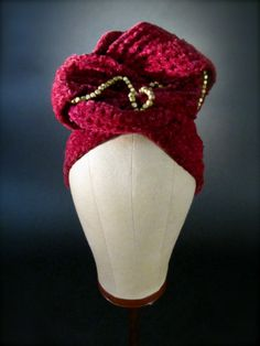 Casper Davis Turban, circa 1945. With WWII came a serious shortage of materials used to craft fashion.  About the time hairpins disappeared all together from the markets, turbans such as this one made its debut, allowing a woman to hide her undressed hair yet dress up her outfits all the while rationing.  The high style turban was hand crafted with crushed knit burgundy velvet and embellished with brass beads.  Padded at the top.