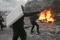 A man pointed a handgun during a clash with police in Kiev, Ukraine, on Jan. 22. Efrem Lukatsky/Associated Press