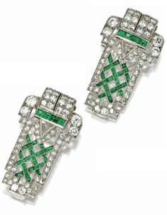 A pair of Art Deco Diamond and Emerald Clips, Cartier, circa 1925. Of modified buckle design, pierced in a lattice motif, set with 2 triangular-shaped diamonds and numerous old European-cut and single-cut diamonds altogether weighing approximately 3.50 carats, accented with calibré-cut emeralds, mounted in platinum, signed Cartier. #Cartier #ArtDeco #Clips