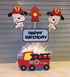 This centerpiece features two Dalmatian puppies with fireman helmets, two hydrants and a Happy Birthday sign., all attached to dowels. The