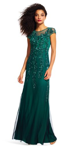 Decadent vines creep down the length of this formal gown. Featuring a sheer neckline and short sleeves, this dress is sophisticated and stunning. Vine beaded accents and a keyhole back complete this evening dress. Paired with a neutral peep toe heel and a matching handbag, this dress is ready for an evening out.