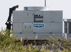 A migrant is hoisted on top of an industrial cooler as more than a dozen migrants gather near trucks which wait on the road that leads to the Channel tunnel in the hopes of boarding them to make a clandestine crossing to England, in Calais, France, May 22, 2015. REUTERS/Pascal Rossignol