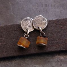 earrings, handmade of oxidized sterling silver (925), natural, dark brown leather +raw Baltic ambers signed © ewa lompe  D E T A I L S : amber (diameter ): 7 mm total length : 2 cm or 0.8   *The amber is a lightweight stone, every piece of amber is unique, so the item you receive will be similiar but not identical to the photo. Please be aware that each earring is made by hand and so there will be slight variatons in eaach piece.  S H I P P I N G : All objects are carefully wrapped in a…